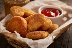 Close up of chicken nuggets in basket with parchment paper and chili tomato sauce on wooden background.