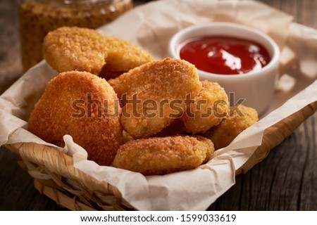 Close up of chicken nuggets in basket with parchment paper and chili tomato sauce on wooden background. Сток-фото ©