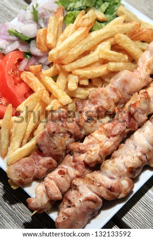close up of chicken skewers served on a plate with fried potatoes and vegetables
