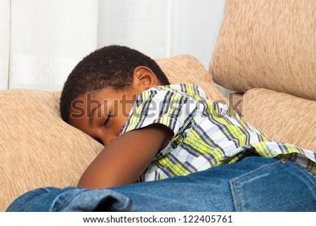 Close up of child boy sleeping on sofa.
