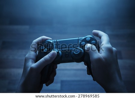 Close up of child hands playing the video game at night
