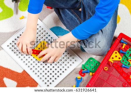 Close up of child hands playing with toys tool kit. Top view #631926641