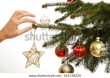 Close-up of child hanging decorative toy ball on Christmas tree branch