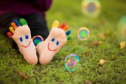 Close up of child human pair of feet painted with smiles outdoor in sunny park with bubble