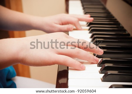Close up of child's hands playing the piano