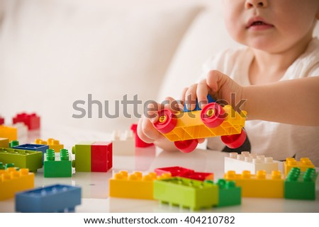 Close up of child\'s hands playing with colorful plastic bricks at the table. Toddler having fun and building out of bright constructor bricks. Early learning.  stripe background. Developing toys