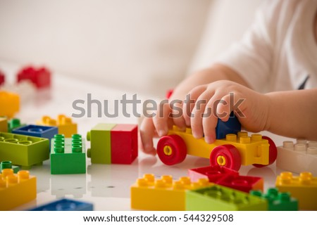 Close up of child's hands playing with colorful plastic bricks at the table. Toddler having fun and building out of bright constructor bricks. Early learning.  stripe background. Developing toys #544329508