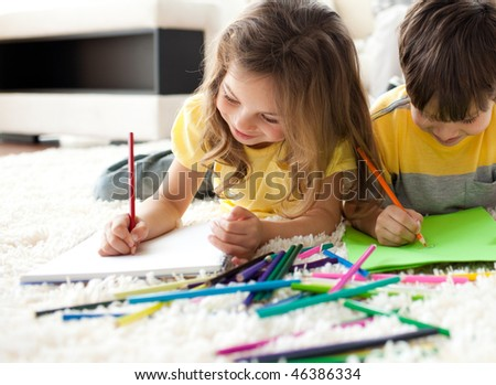 Close-up of children drawing lying on the floor in the living room