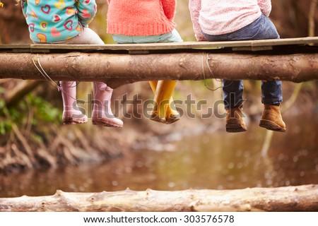Close Up Of Children\'s Feet Dangling From Wooden Bridge