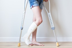 Close-up of children's feet, one leg is broken and in a cast, next to crutches. Light background.