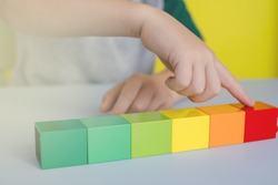 close up of children's hands counting colored blocks in lines on the table