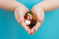 Close-up of children's hands in the palms are holding colored candies and gummies. Horizontal photo, soft focus, selected focus. Photo in pastel colors