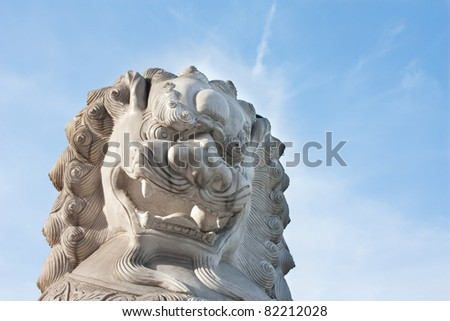 Close-up of chinese imperial lion statue with blue sky in the background