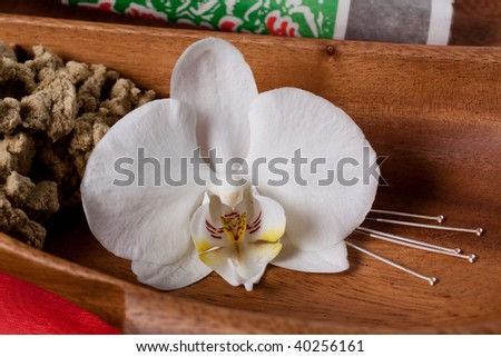 Close up of chinese medicine tools, needles, Moxa and an orchid flower