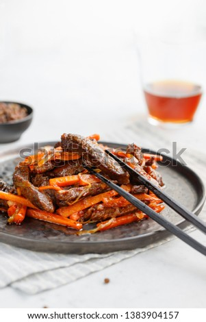 Close-up of Chinese spicy Szechuan beef meal on a black plate with wooden sticks over white table. Asian food recipe; portion for one person.
