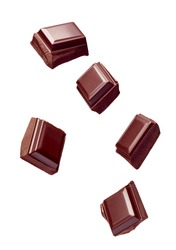 close up of chocolate pieces stack falling on white background
