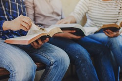 close up of christian group hold and opening bible page while reading and study bible together with friends in Sunday school class room