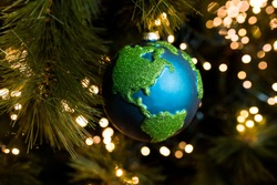 Close-up of Christmas bauble decoration ornament globe planet earth  on the background of the Christmas tree. Merry christmas and new year concept. Selective focus