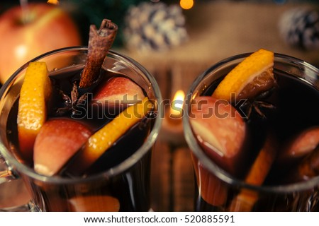 Close up of Christmas mulled wine with fruits, candles  and spices background. Winter warming drink with recipe ingredients. Top view. Two cup.
