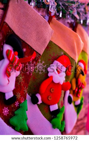 Close-up of Christmas socks for gifts on the fireplace on New Year's Eve for Santa Claus with a snowman #1258765972
