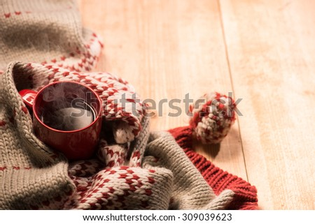 Close up of Christmas warm scarf and a red cup of hot drink are situated on floor