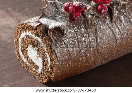 Close up of Christmas Yule chocolate log decorated with dipped holly leaves and berries, dusted with icing sugar