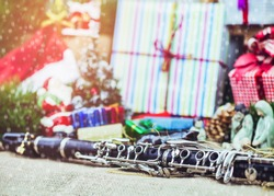 close up of clarinet with blurred Christmas tree and decoration with gift boxes background, Snow falling in foreground
