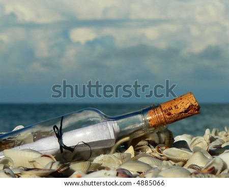 Close up of clear bottle with message inside laying on some shells by the ocean. The bottle is corked. There is sunshine on the beach of the shells and bottle, but a cloudy sky is over the ocean.
