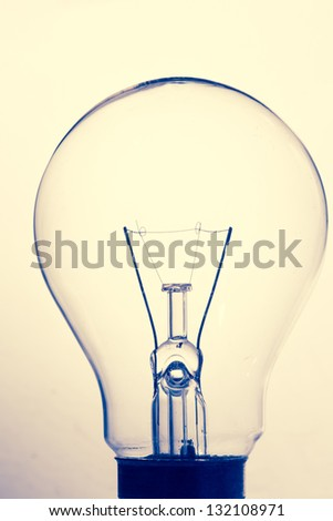 Close up of clear light bulb standing in sepia with blue tones