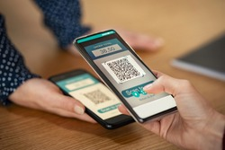 Close up of client hand holding phone and scanning qr code to transfer money. Girl hands holding smartphone to scan code for digital payment. Screen scanning with smartphone for qr-code payment.
