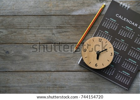 close up of clock, calendar and pencil on the table, planning for business meeting or travel planning concept