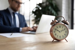 Close up of clock on forefront with businessman work on laptop online in office on background. Male employee prepare project at workplace, try meet deadline or appointment. Time management concept.