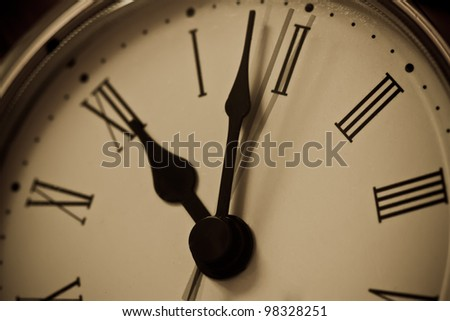 Close up of clock with hands showing a little after midnight and with movement of second hand.