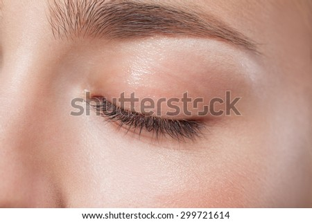 Close up of closed eye of young beautiful woman with perfect day makeup eye shadows