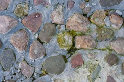 Close up of cobblestones on sidewalk, covered in ice. Texture of stone and ice.