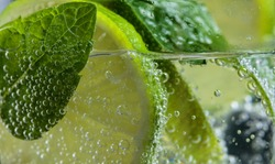 Close up of cocktail with lime , ice  and mint leaves .