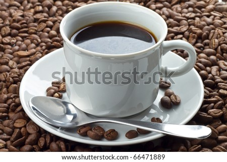 Close up of coffee beans and black coffee. Beans in and around the white saucer with the cup and spoon