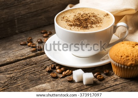 Close-up of coffee cup with roasted coffee beans on wooden background. #373917097