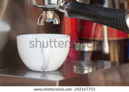 close up of coffee machine makes coffee and white cup
