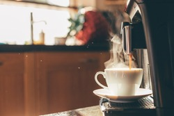 Close-up of coffee machine making steaming coffee on vintage kitchen. Early morning breakfast on rustic background, picture with copy space