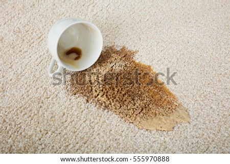 Close-up Of Coffee Spilling From Cup On Carpet #555970888
