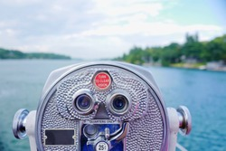 Close up of coin-operated binocular on cruise ship against green plants covered lake shore. Travel background. Selective focus.