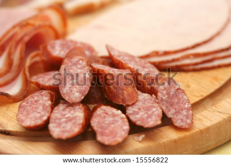 Close-up of cold cuts on wood plate.