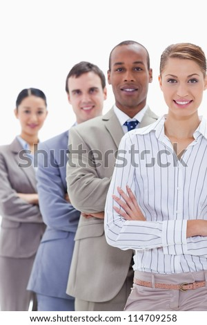 Close-up of colleagues smiling in a single line crossing their arms with focus on the first woman