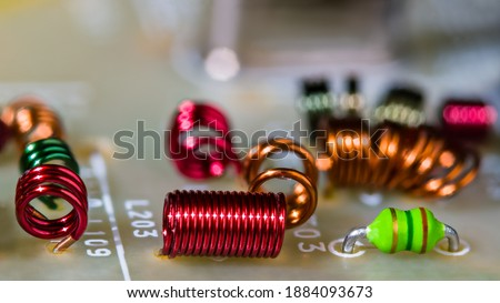 Close-up of colored air-core coils wire windings for receiving radio-frequency signal. Circuit board detail with RF electronic inductors inside dismantled TV device module. Side view. Selective focus. Stok fotoğraf ©