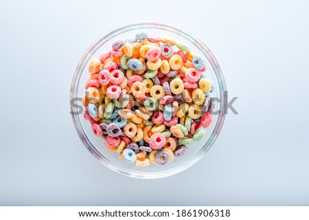 Photo of  Close up of colored fruit cereal loops in bowl .on a blue background.top view