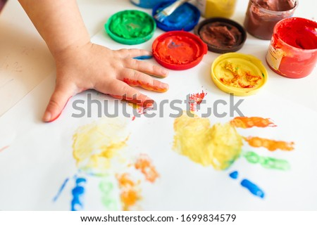 Close up of colored hand print on white background. Ideas for drawing with finger paints. Finger painting for kids. Little girl painting by finger hand paint color. Children development concept.
