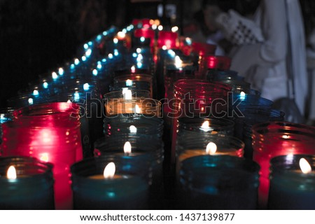 Close up of colorful candles in a dark spiritual scene. Commemoration, funeral, memorial. Religious symbolism. #1437139877