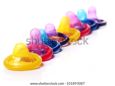 Close up of colorful condoms over white background