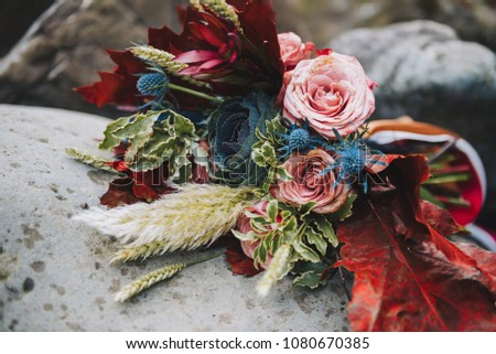 Close up of colorful elegant modern fall wedding bouquet in red, marsala, burgundy